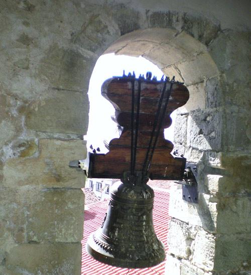 Campana pequeña. Sobre el sillar que recibe el eje izquierdo, otro con inscripción colocado bocabajo.
