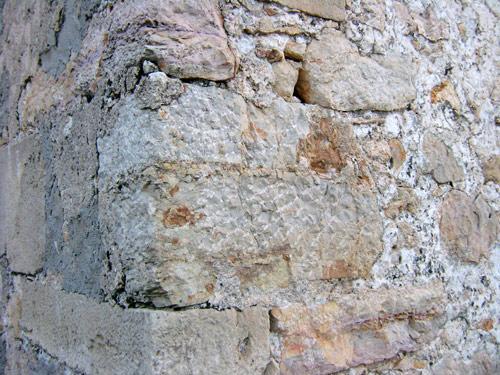 Fachada sur de la capilla de los Rihuete.    Arriba un sillar nuevo toscamente labrado. Abajo uno reutilizado.