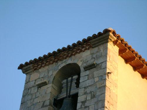 Fachada sur del campanario. Canecillos en los extremos y colocados como elemento decorativo al lado del hueco de las campanas. El resto de la cornisa es de teja vuelta.